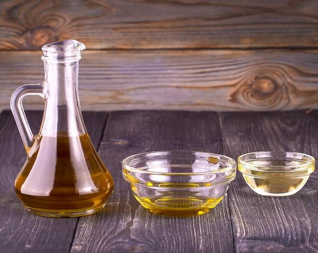O óleo vegetal de cozinha em um pequeno copo de vidro e jarro na velha mesa de madeira
