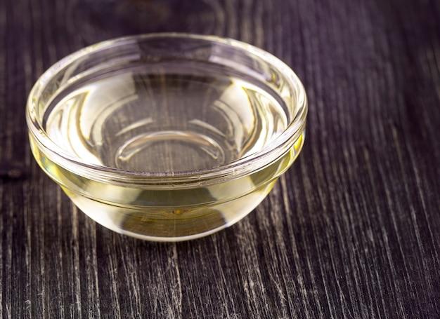 O óleo vegetal de cozinha em um pequeno copo de vidro na velha mesa de madeira