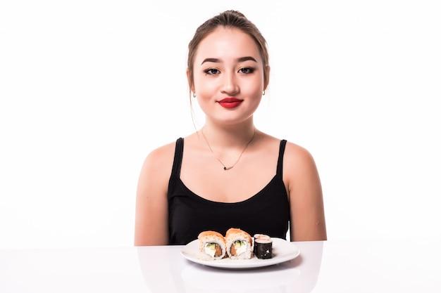 O olhar consideravelmente asiático com penteado modesto senta-se na tabela come rolos de sushi sorrindo isolado no branco