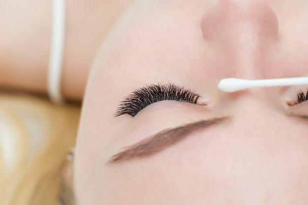 O olho com os cílios estendidos está lacrimejando. o mestre enxuga um olho úmido com um cotonete. alergia. olhos sensíveis.