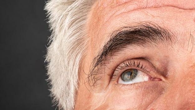 O olho de um homem idoso fecha as rugas e o conceito de envelhecimento dos pés de galinha