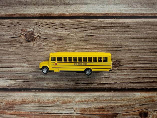 O ônibus escolar na mesa de madeira para a educação ou o conceito de volta às aulas
