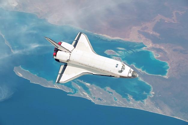 O ônibus espacial voa sobre a bela vista aérea do planeta terra com o mar e as ilhas. foguete espacial no céu sobrevoar o continente explora o espaço e os planetas. tiro aéreo