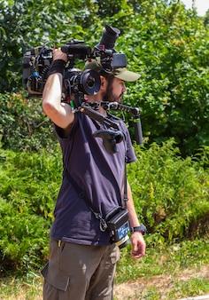 O operador de câmera assistente com controle de foco sem fio mantém a câmera no ombro antes de fotografar.