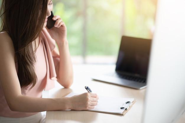 O operador está conversando com o cliente dela. ela está gravando pedidos do cliente em papel.