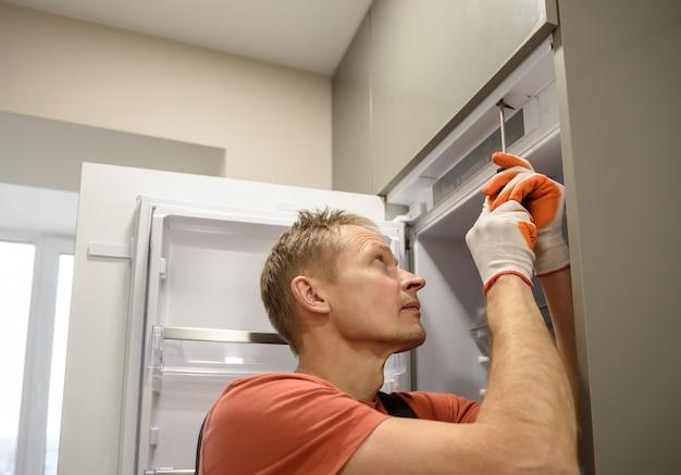 O operário está consertando a geladeira embutida nos móveis da cozinha.