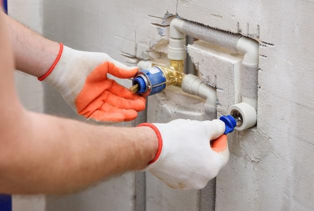 O operário está instalando um tampão na tubulação da torneira embutida.