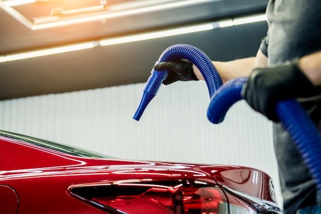 O operário faz a secagem automática do carro após a lavagem.