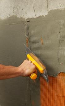 O operário realiza o reforço e enchimento das paredes. foco seletivo.