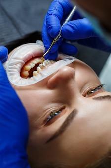 O ortodontista coloca aparelhos de metal nos dentes do paciente. tratamento odontológico ortodôntico. foto de alta qualidade