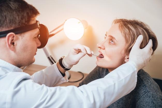 O otorrinolaringologista examina a garganta da mulher com uma espátula médica.