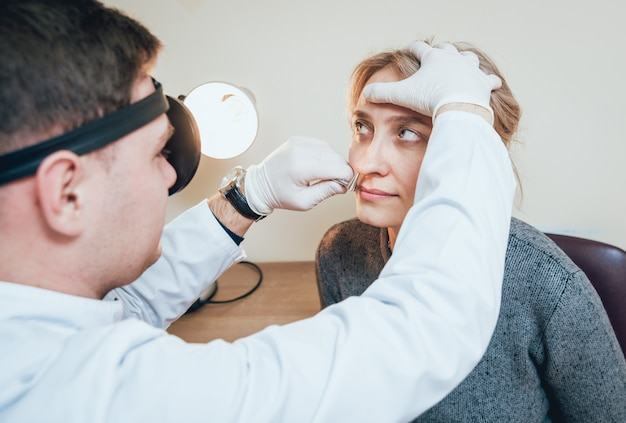 O otorrinolaringologista examina o nariz da mulher com dilatador nasal.