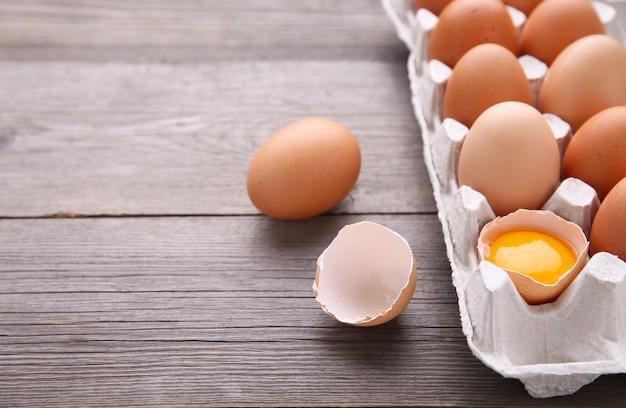 O ovo da galinha é meio quebrado entre outros ovos. ovos de galinha em recipientes no fundo cinza de madeira