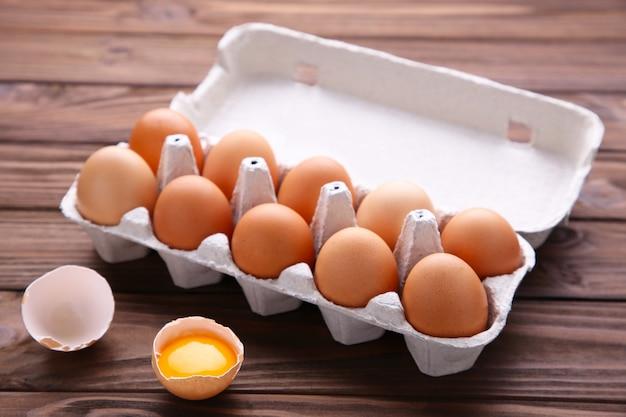O ovo da galinha é meio quebrado entre outros ovos. ovos de galinha em recipientes no fundo de madeira marrom