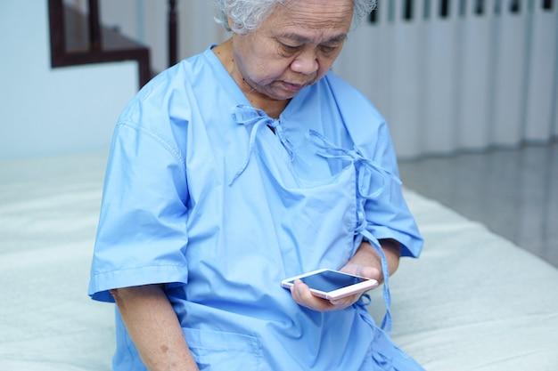O paciente asiático da mulher idosa ou idosa da senhora idosa leu o email no telefone celular.