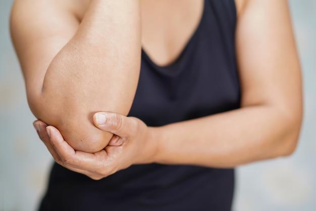O paciente asiático da senhora de meia idade toca e sente a dor seu cotovelo e braço.