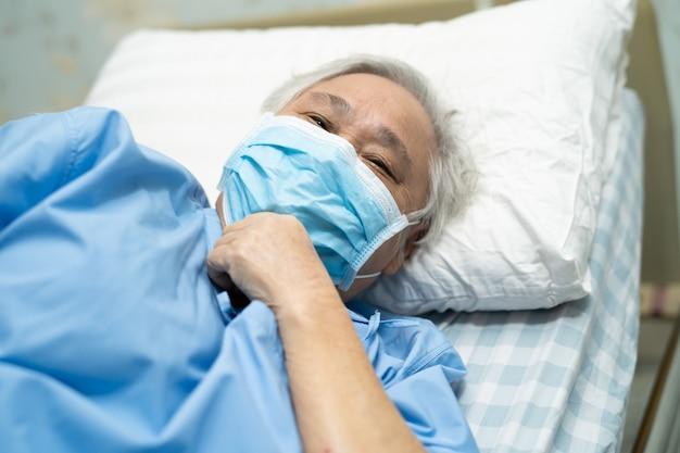 O paciente asiático sênior da mulher que veste uma máscara protetora no hospital para protege o vírus de coronavirus covid-19.