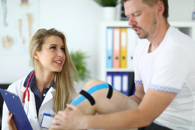 O paciente com fita adesiva kinesio tem um médico no joelho ao lado dele. conceito de serviços médicos