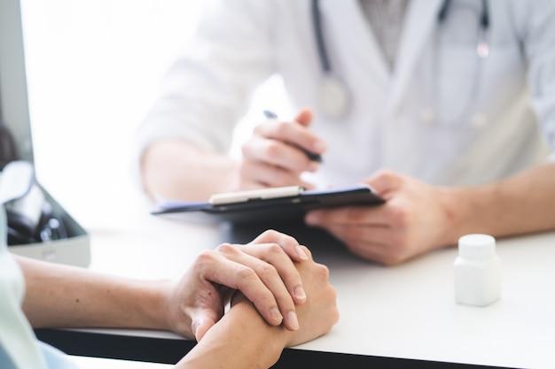 O paciente de escuta do doutor explica seus sintomas e notas ao registro médico.