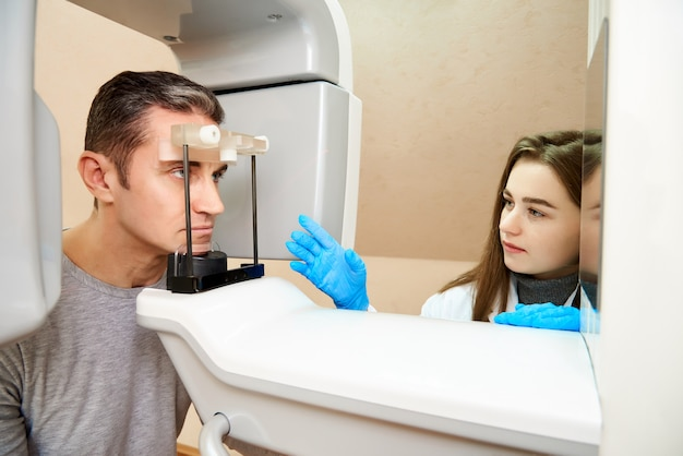 O paciente do sexo masculino está no scanner e o girldroctor está perto do painel de controle.