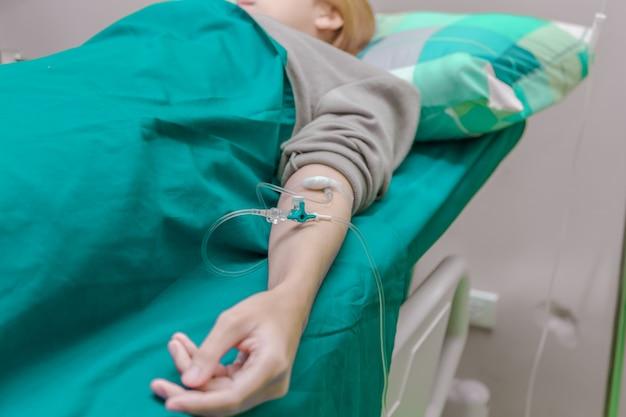 O paciente está em gotejamento recebendo uma solução salina no hospital.