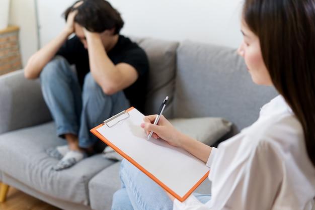 O paciente masculino novo que senta-se no sofá com cara triste está tendo o consultante pela fêmea profissional do psicólogo.