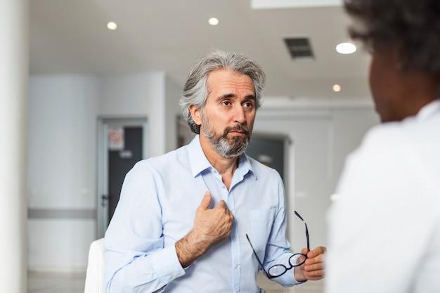 O paciente reclama com o médico sobre sua dor e outros sintomas
