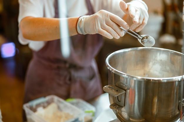 O padeiro com luvas derrama o ingrediente em pó na tigela fazendo massa na oficina