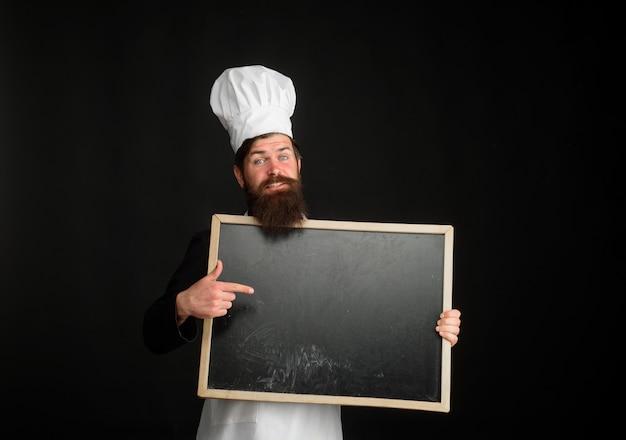 O padeiro ou cozinheiro mestre mostra o sinal do menu, o chef profissional do quadro-negro, no menu da cozinha vazia