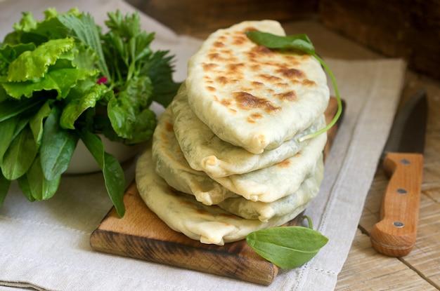 O padeiro que faz o prato tradicional dos armênios dos chapéus artsakh zhingyalov é um tipo de pão recheado com ervas.