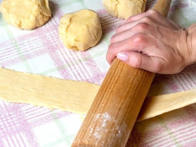 O padeiro rola a massa em tiras na mesa da cozinha, polvilhada com farinha.