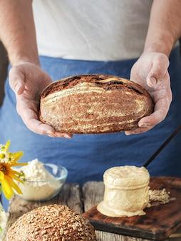 O padeiro segura pão artesanal caseiro nas mãos