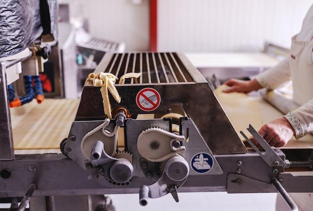 O padeiro trabalhador no uniforme branco que faz torta crostas na máquina na padaria.
