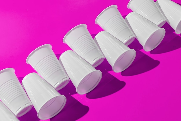 O padrão abstrato de copos de plástico na superfície colorida com sombras duras da moda