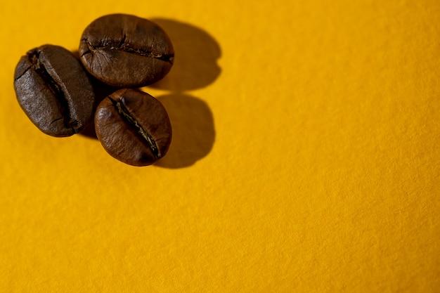O padrão de grãos de café em fundo colorido
