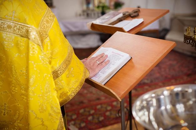 O padre colocou a mão sobre a bíblia sagrada na igreja ortodoxa
