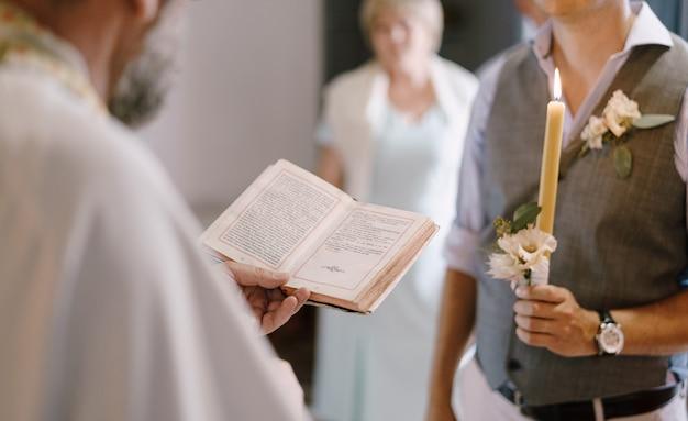 O padre com a bíblia fica ao lado do noivo com uma vela na mão