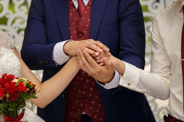 O padre mantém as mãos da noiva e do noivo juntos enquanto dá uma bênção