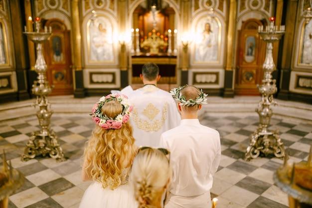 O padre, o noivo e a noiva em grinaldas estão no altar da igreja de são nicolau em
