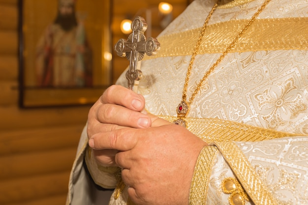 O padre segura um crucifixo nas mãos