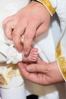 O padre toca a perna do bebê durante o batismo