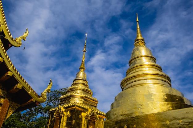 O pagode de ouro e céu azul no wat phra singh