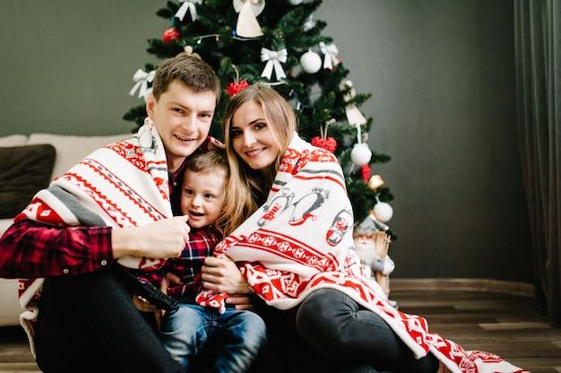 O pai, a mãe segura o filho sentado perto da árvore de natal. feliz ano novo e feliz natal. interior decorado de natal. o conceito de férias em família. retrato. metade superior. fechar-se.