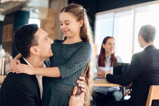 O pai adulto abraça a filha pequena, estando no primeiro plano.