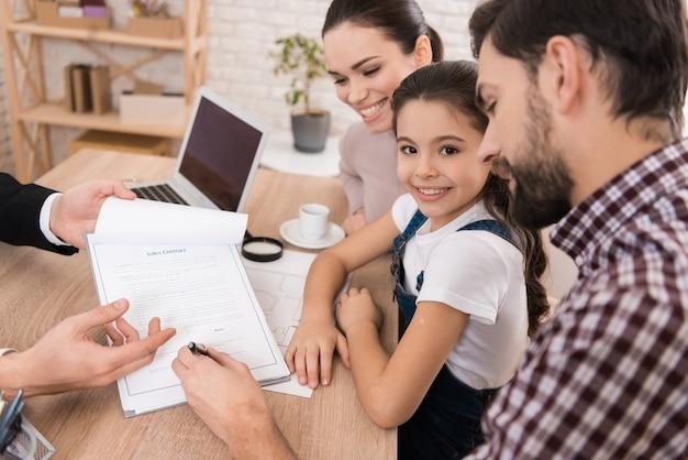 O pai adulto com esposa e filha assina o contrato de vendas.