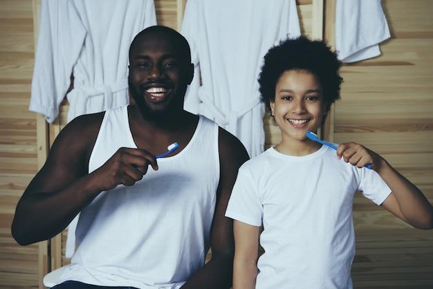 O pai afro-americano e o filho pequeno escovam os dentes.