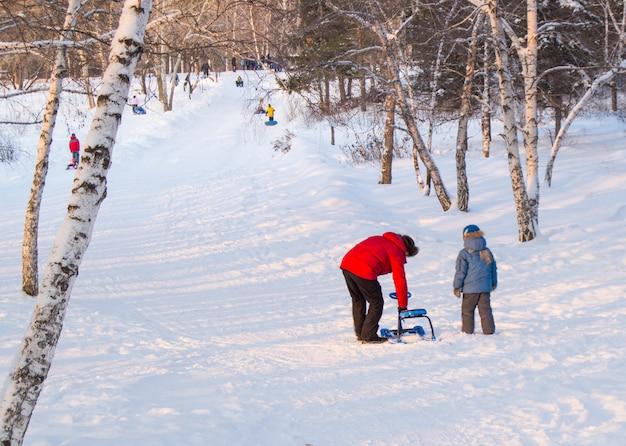 O pai ajuda o filho a corrigir o snowmobile, colina abaixo