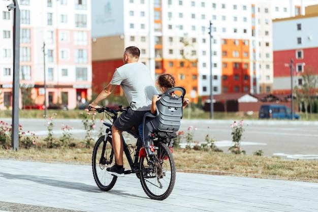 O pai anda de bicicleta, a filha pequena na cadeirinha infantil