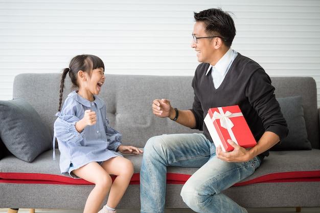 O pai asiático dá o presente para a filha. caixa de presente surpresa conceito para o aniversário.