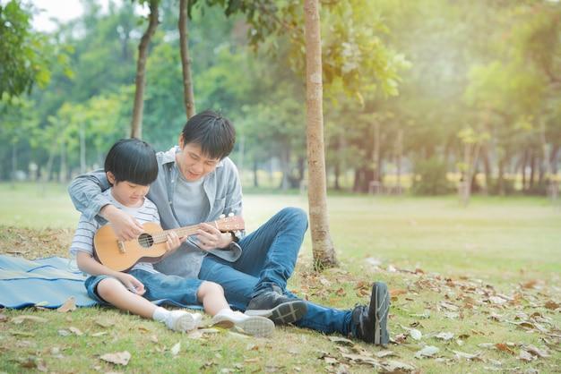 O pai asiático ensina o filho a tocar guitarra no parque público, a paternidade feliz da união tem a atividade do piquenique no jardim ao ar livre.